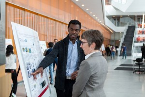 Tagbo Niepa, REACT Fellow, shares his poster with REACT Faculty, Karen Winey.